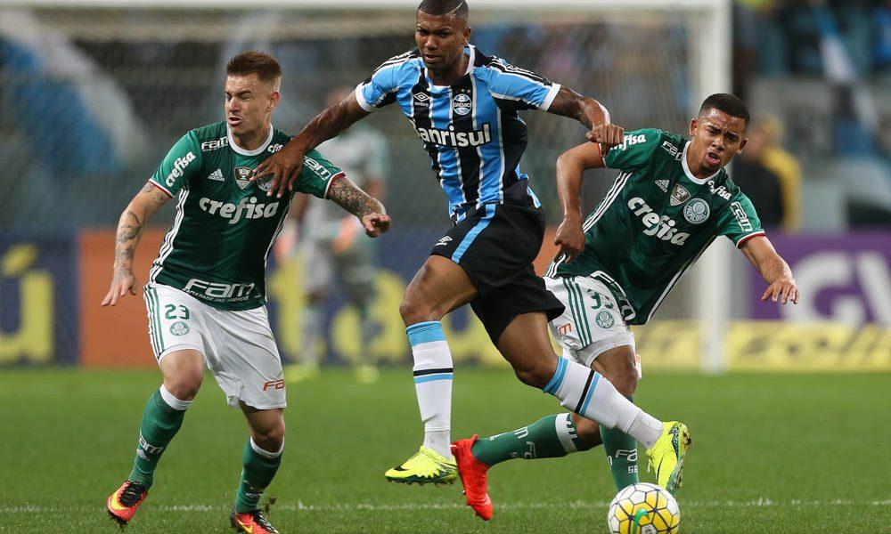 Os jogadores Róger Guedes e Gabriel Jesus (D), da SE Palmeiras, disputam bola com o jogador Walace, do Grêmio FPA, durante partida válida pela vigésima quarta rodada, do Campeonato Brasileiro, Série A, na Arena do Grêmio.